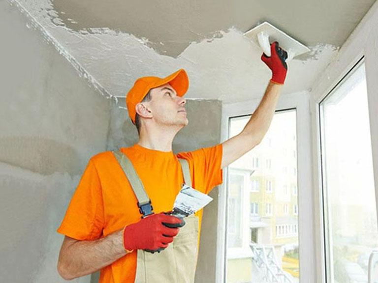 мастер шпатлюет потолок